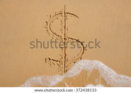 Dollar sign in beach sand being washed away by wave  - stock photo