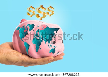 Dollar sign over piggy bank with world map in male hand on blue with clipping path ( map derived from NASA world map) - stock photo