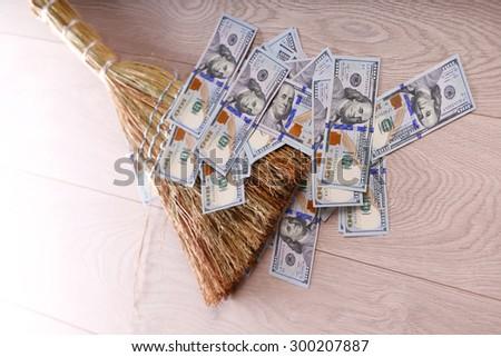 Dollars and broom on wooden floor, closeup - stock photo