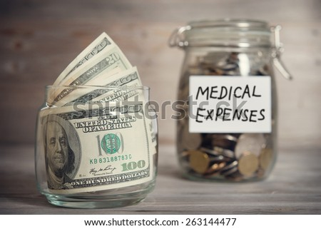 Dollars and coins in glass jar with medical expenses label, financial concept. Vintage tone wooden background with dramatic light. - stock photo
