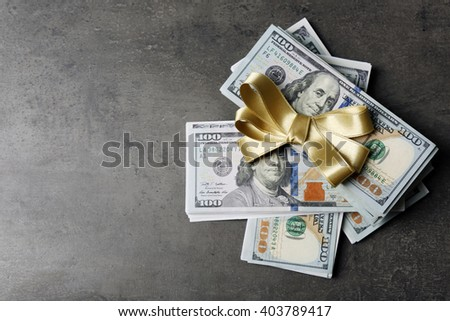 Dollars and colorful bow on grey background - stock photo