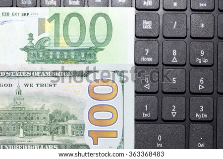 dollars and euros on a laptop keyboard - stock photo