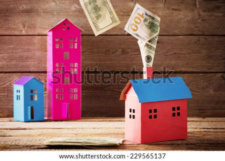 Dollars banknotes falling from house on wooden background - stock photo