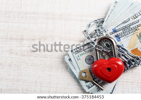 Dollars currency with lock and chain on wooden table background - stock photo