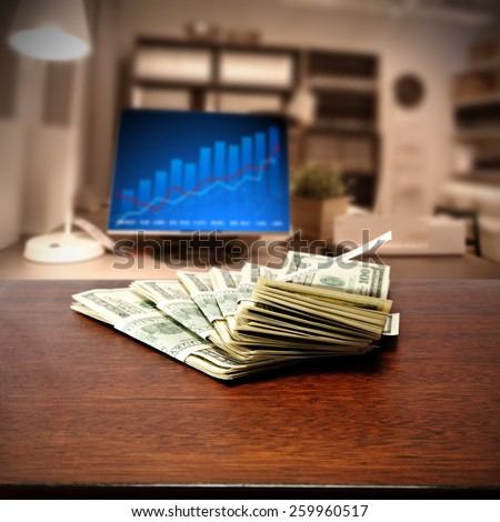 dollars on brown table and computer background  - stock photo