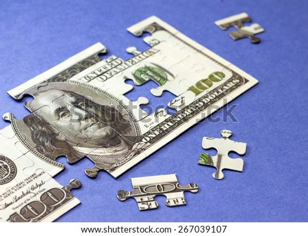 Dollars puzzle. Concept of finance and savings. On blue background - stock photo