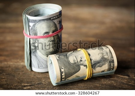 Dollars roll on wooden background - stock photo