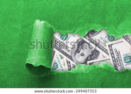 Dollars through torn green paper - stock photo