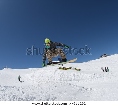 """DOMBAI, RUSSIA - APRIL 6: Georgy Kuznetsov in the annual competition """"Flammable Camp Dombai 2009"""" jumping from a few snowy hills, which was held April 6, 2009 in Dombai, Russia - stock photo"""