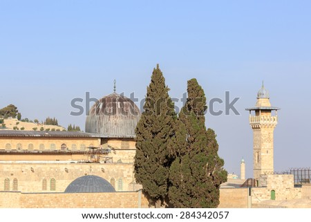 Dome of mosque of Al-aqsa with minaret and cypresses in Jerusalem - stock photo