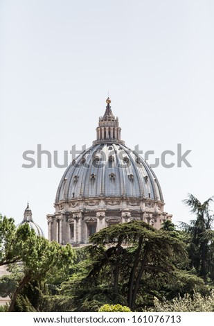Dome of Saint Peter's Basilica rising from the trees in Vatican city - stock photo