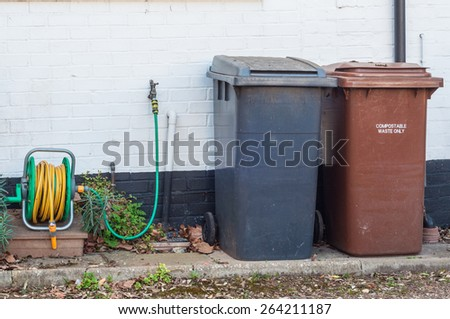 Domestic plastic recycling and disposal bins and watering hose against a brick wall - stock photo