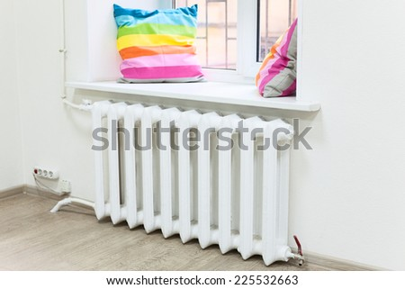 Domestic room interior with central heating radiator under window - stock photo