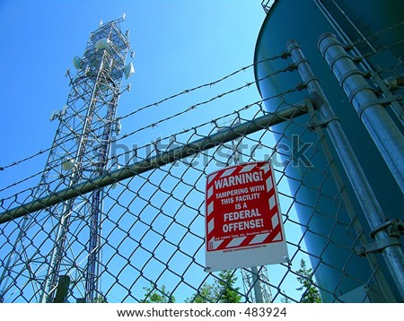 Domestic Terrorism Targets, Warning sign, Barbed wire fence, towers - stock photo