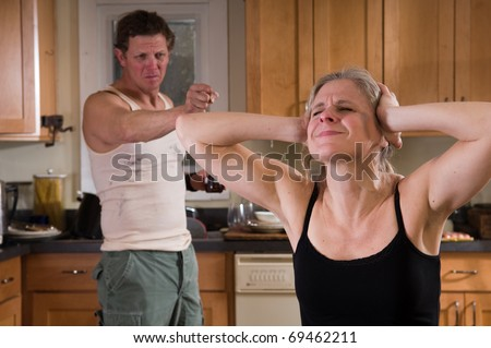 domestic violence - husband yelling at wife (bruise on her face) as she covers her ears - stock photo
