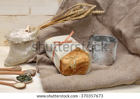 Domestic whole grain bread with pumpkin, flax, sunflower and sesame seeds on jute cloth with sack of whole grain flour and sifter - stock photo