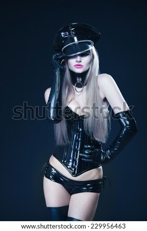 Dominating vamp girl in a black shiny latex corset with a military hat on the head - stock photo