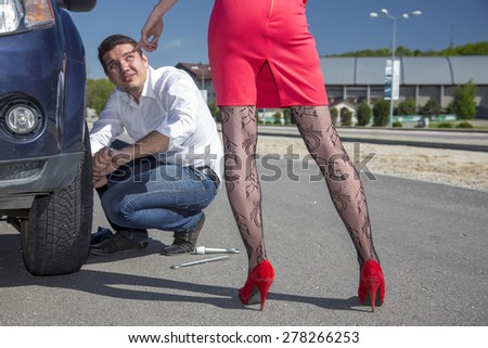 Dominatrix female directs man to repair car. Leggy female body sexy stockings pointing her hand towards car wheel to be fixed by conformable man roadside outdoor sunny day blue sky - stock photo