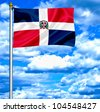 Dominican Republic waving flag against blue sky - stock photo