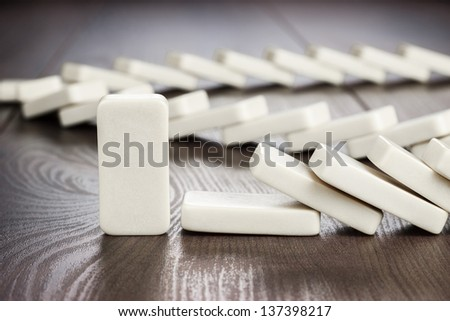 domino piece standing still concept on wooden table - stock photo