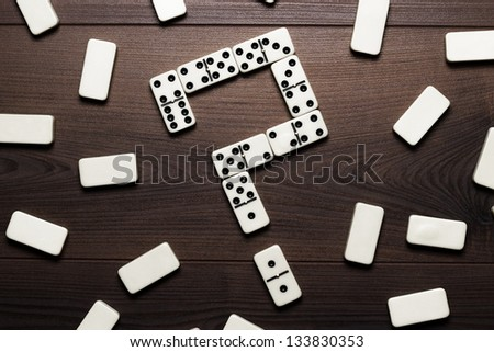 domino pieces forming question mark over wooden table - stock photo