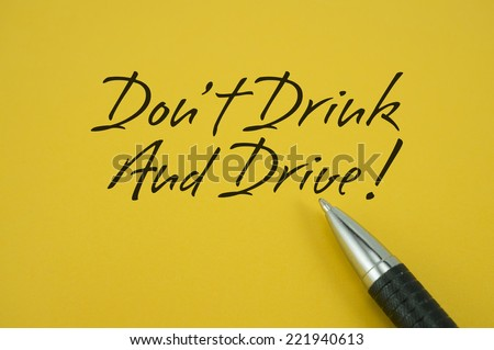 Don't Drink And Drive! note with pen on yellow background - stock photo