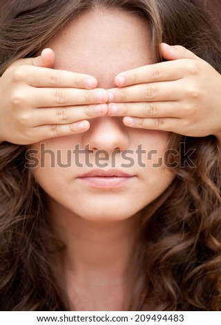 Don't look! Younger sister closed eyes of her older sister by hands - stock photo