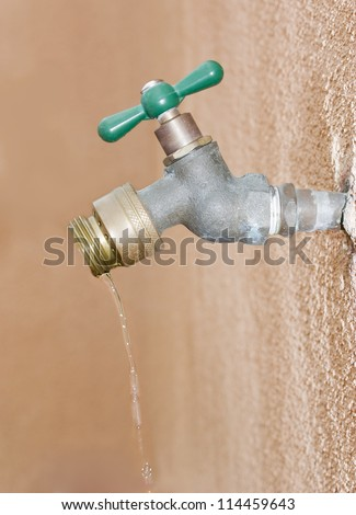 Don't waste water! Wasting water depicted by a leaking outdoor wall valve. Valve is attached to a pipe embedded in the stucco as water drips from the spout. - stock photo