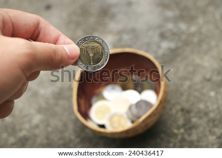 Donate some coin to beggar in coconut shell container - stock photo