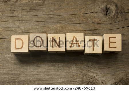 Donate text on a wooden background - stock photo