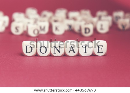 Donate word written on wood cube with red background - stock photo