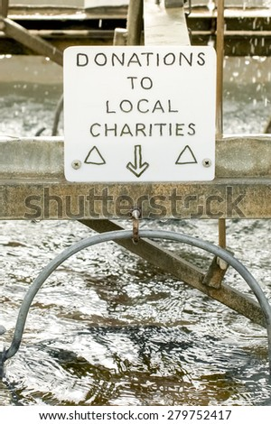 donation sign above a charity wishing well - stock photo