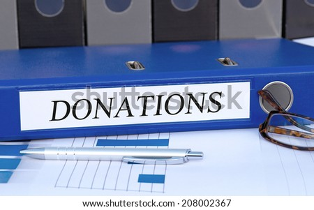 Donations - blue Binder in the Office - stock photo