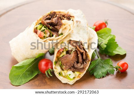 Doner kebab with cherry tomatoes and salad on wooden background. Natural light, horizontal - stock photo