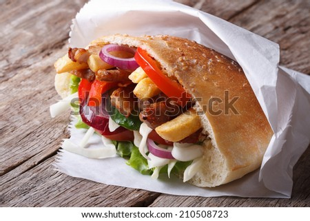 doner kebab with meat, fried potatoes and vegetables in pita bread close-up on an old table horizontal - stock photo
