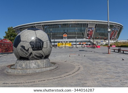 """Donetsk, Ukraine - August 22, 2015: Empty during the war the stadium """"Donbass Arena"""" with a sign located on its territory for humanitarian Staff Rinat Akhmetov - stock photo"""