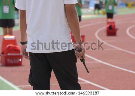 DONETSK, UKRAINE - JULY 11: Official with starting pistol before the 110 meters Hurdles competition during 8th World Youth Championships in Donetsk, Ukraine on July 11, 2013 - stock photo