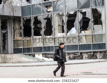 DONETSK, UKRAINE - March 4, 2015: A man walks past the destroyed building Chamber of Commerce, Kiev Avenue, Donetsk.  -- This area is adjacent to the Donetsk airport named after Sergei Prokofiev.  - stock photo