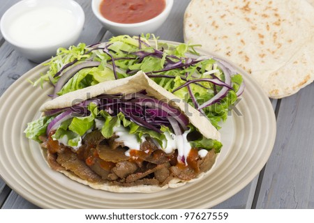 Donner Kebab - Turkish donner meat in a pitta bread served with chili sauce, garlic mayonnaise and crunchy salad. - stock photo
