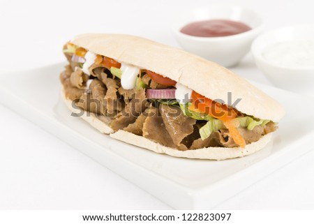 Donner meat with salad in a flatbread on a white background. Chilli sauce and yoghurt on side. - stock photo