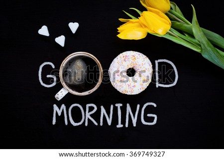 Donut (doughnut), cup of coffee, flower yellow tulip and heart shaped sugar cubes. Good morning greeting on black chalk board. Top view, flat lay - stock photo