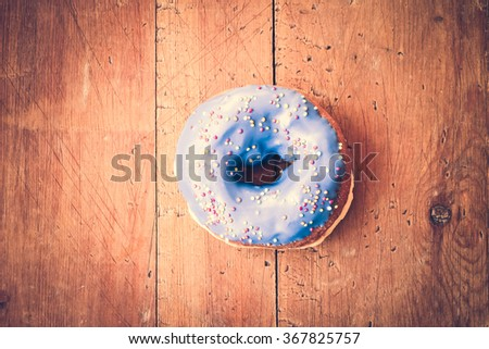 Donut. Sweet icing sugar food. Dessert colorful snack. Glazed blue sprinkles. Treat from delicious pastry breakfast. Bakery cake. Doughnut with frosting. Baked unhealthy round.  - stock photo