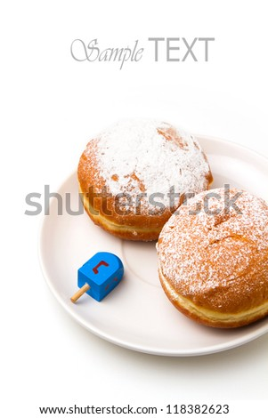 Donut with dreidel on plate. Hanukkah holiday. - stock photo