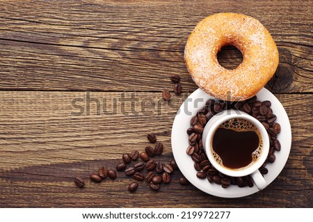 Donut with sugar and cup of hot coffee on old wooden table. Top view - stock photo