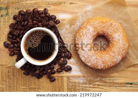 Donut with sugar and cup of hot coffee on wooden table. Top view - stock photo