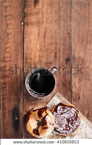 Donuts and black coffee over rustic background. Image shot from overhead. - stock photo