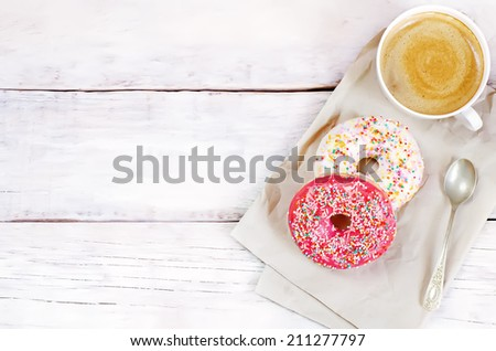 Donuts and coffee on a white wood background. toning. selective focus on red donut - stock photo