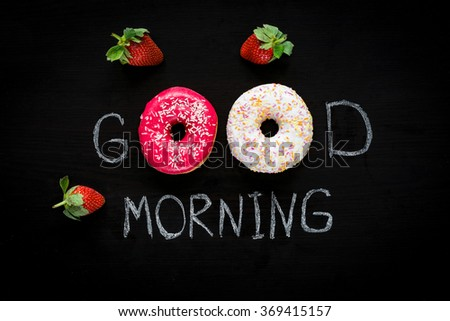 Donuts and strawberries. Good morning greeting written on black chalk board. Table top view. Breakfast food concept, Valentines day food. Flat lay - stock photo