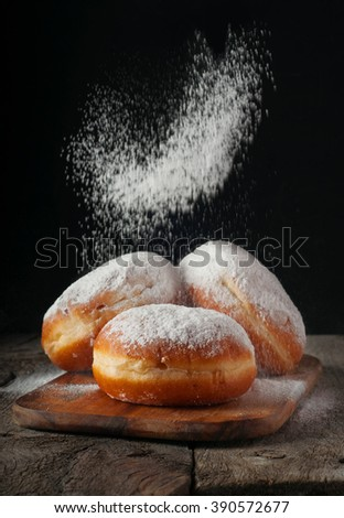 Donuts sprinkled with powdered sugar on wooden table on black background. Food background - stock photo