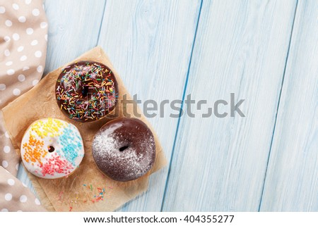 Donuts with colorful decor on wooden table. Top view with copy space - stock photo